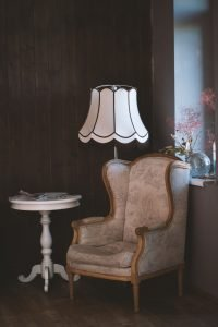 armchair with a floor lamp and a table