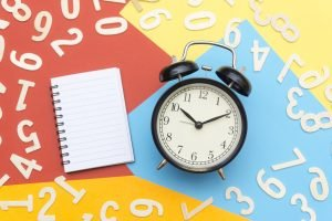clock and notebook on colorful background