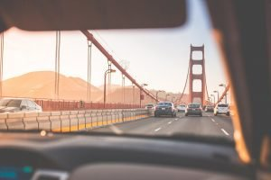 A person in a car on the Golden Gate bridge. Famous sights are just one thing you get to witness after driving long-distance.