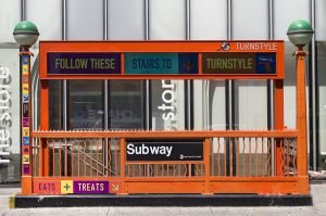 A subway sign on the street.