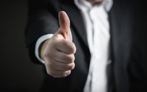A close up of a person in a black suit giving the cameraman thumbs up.