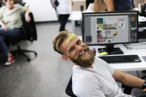 A bearded man laughing in an office in Brooklyn