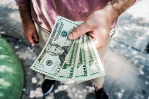 A man in a pink shirt holding 4 dollar bills.
