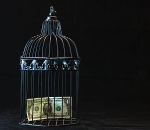 A black steel cage with a dollar bill inside it. If you negotiate your rent, you will save money.
