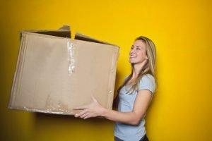 A woman holding a box and smiling, standing in front of a yellow background.