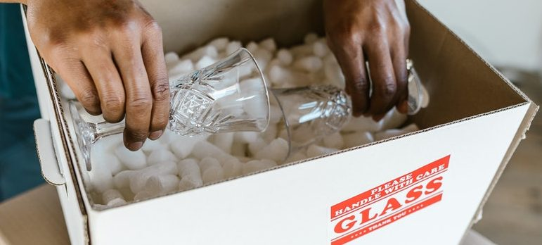 A guy packing glass in a box