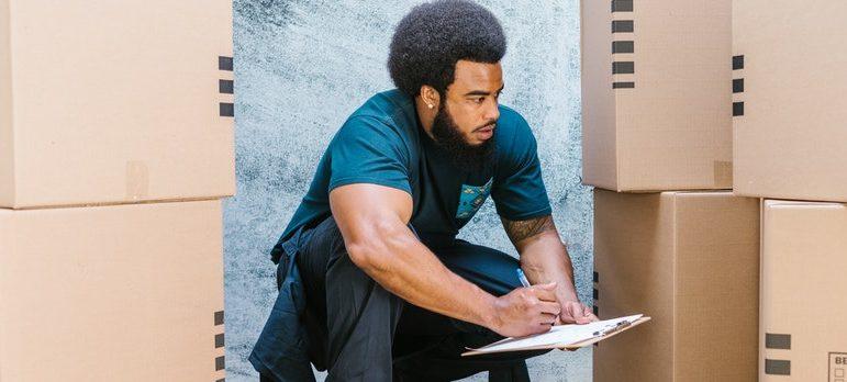 A guy checking out carton boxes