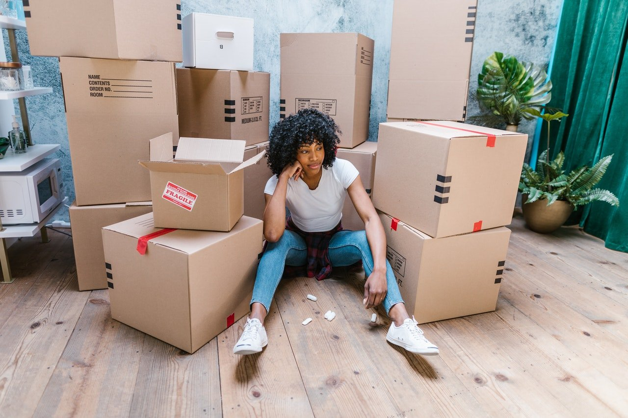 A girl sitting on the floor next to moving boxes