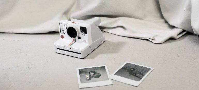 Instant camera on the ground with instant photos next to it and white sheet cover behind.