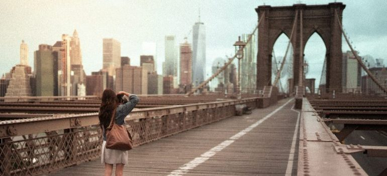 Woman standing on the Brooklyn bridge, taking a picture.