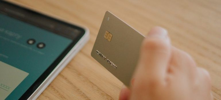 Hand holding a silver debit or credit card and a tablet next to it.