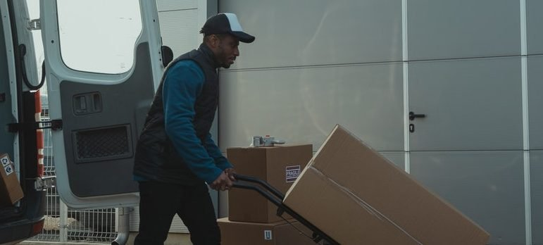 A person using a dolly to move boxes