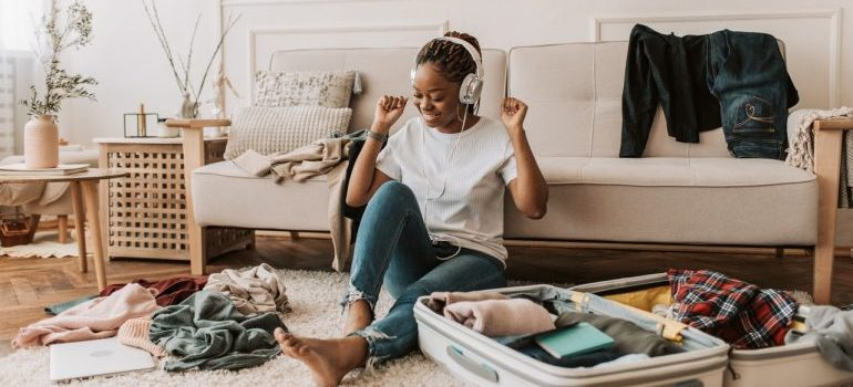A woman listening to music while packing