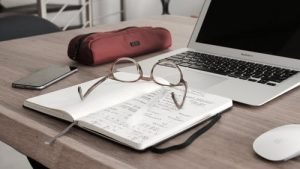 glasses on the notebook next to the laptop