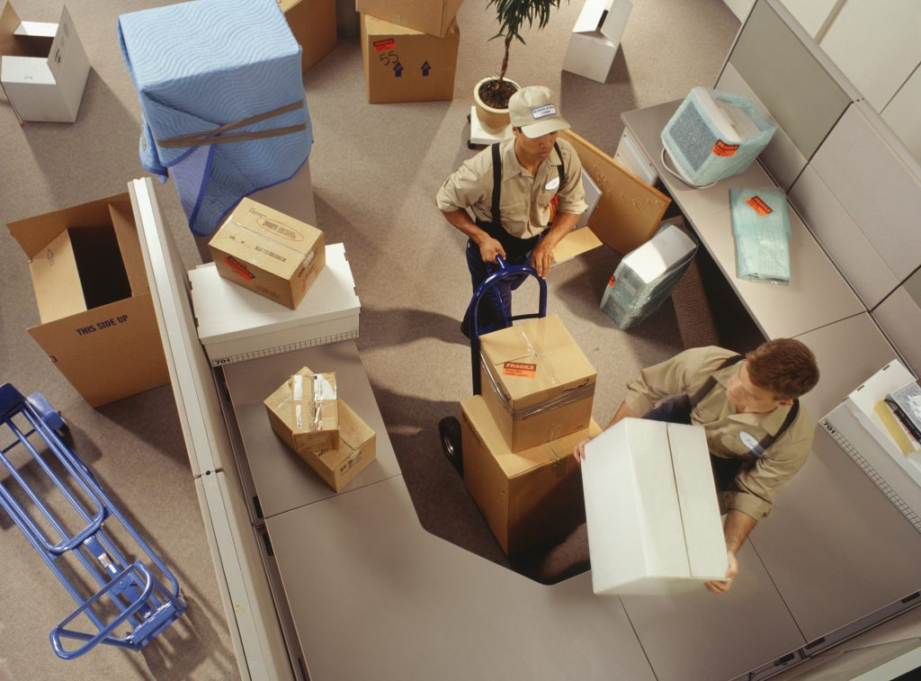 Two removal men moving boxes in office, elevated view