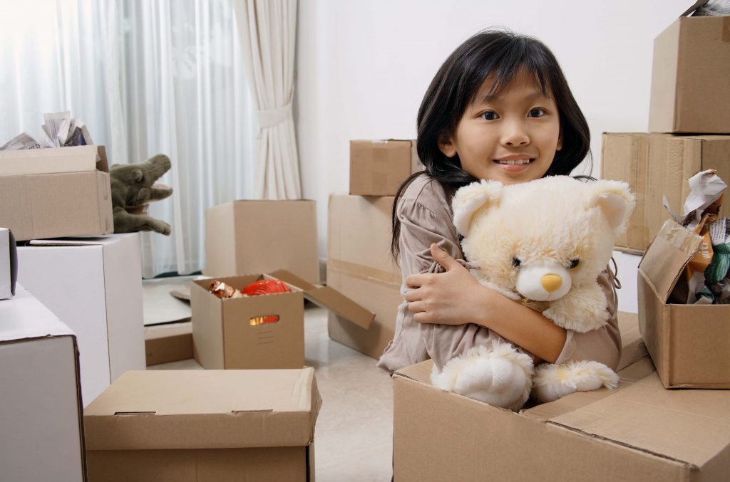 Girl holding teddy bear by moving boxes