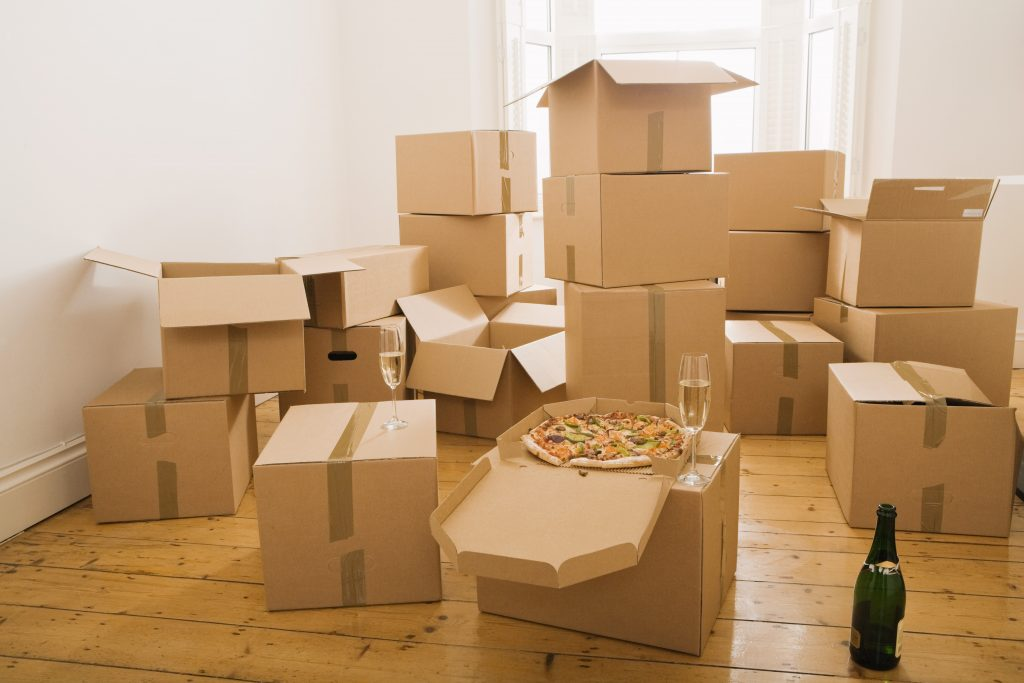 Pizza and champagne on moving boxes