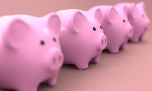 Four pink piggy banks on a pink surface.