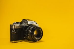 Camera against yellow background.