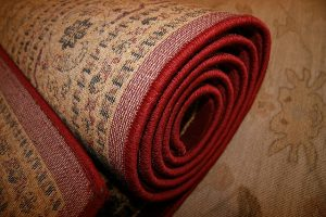 A rolled rug, You need to roll the rug when you want to pack and move large area rugs