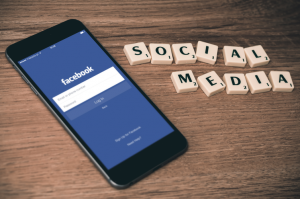 """Phone open to Facebook app log in page next to words """"social media"""" spelled out in Scrabble tiles."""