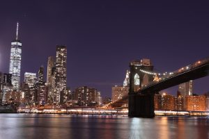 A view of the Brooklyn bridge and a part of the city at night.