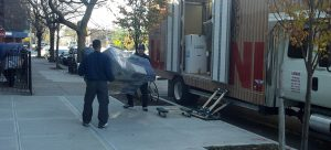 Two of our packing experts loading items onto a moving truck