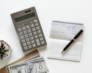 Calculator, money, pen and written cost calculations on a desk next to a wooden, house-shaped paperweight.