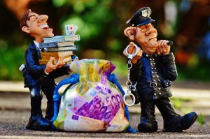 Two figurines. One of a cop holding handcuffs, and another of a man holding books.