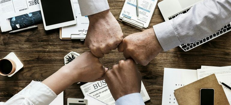 Business people putting fists together in office