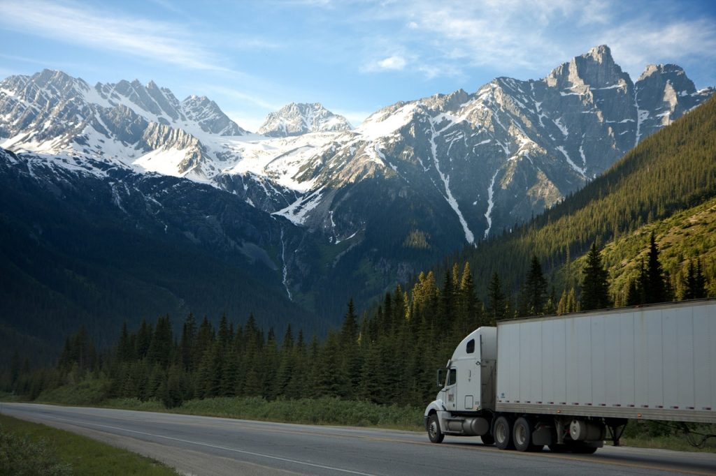 A white truck on the road - because you're renting a moving truck, the DIY method is not the cheapest option