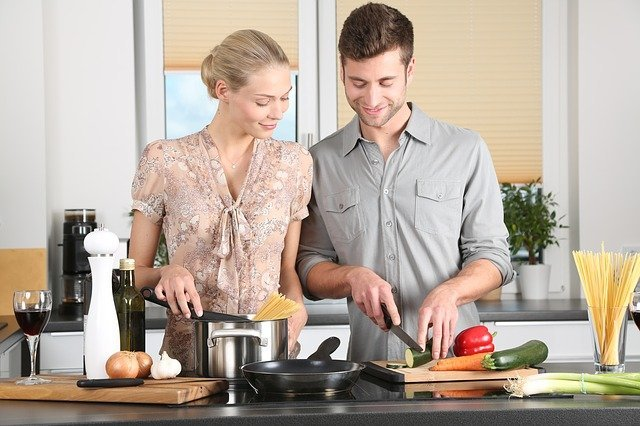 couple preparing a meal after they move in together after a long-distance relationship