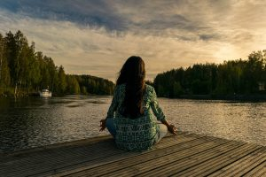 A woman doing yoga on a dock.